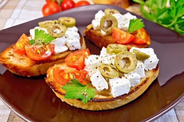 茶色のプレートにフェタチーズ、トマト、オリーブ、ナプキン、リネンのテーブルクロスの背景にパセリとパンのスライス