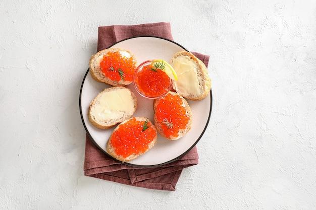 白い背景の上のプレートに赤いキャビアとパンのスライス。上面図。