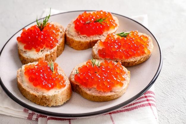 白い背景の上のプレートに赤いキャビアとパンのスライス。