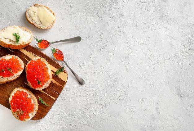 白い背景の上の木製のまな板に赤いキャビアとパンのスライス。上面図。スペースをコピーします。