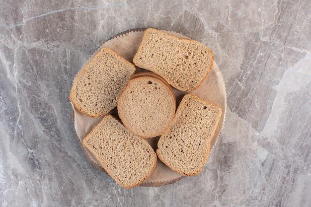 Кусочки черного хлеба на деревянной доске на мраморе.