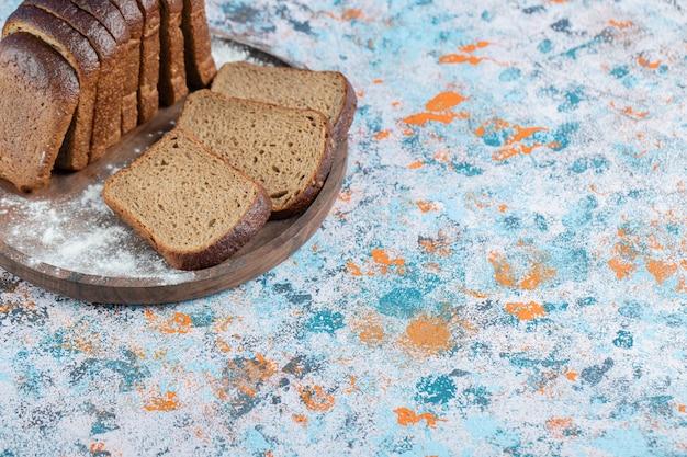 Ломтики ломтиков черного хлеба на деревянной тарелке