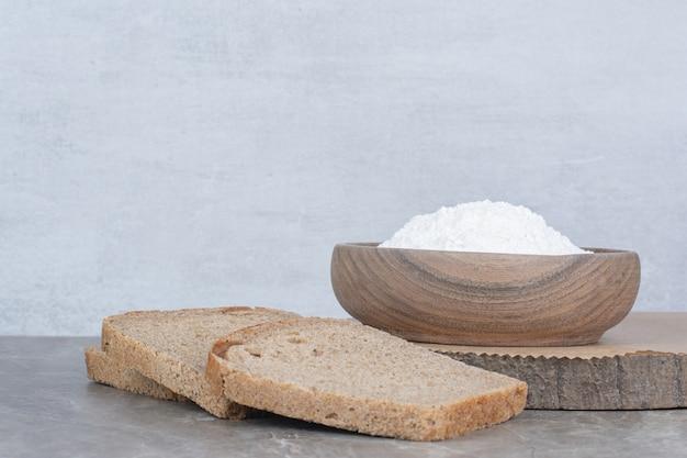 大理石の表面に小麦粉と茶色のパンのスライス