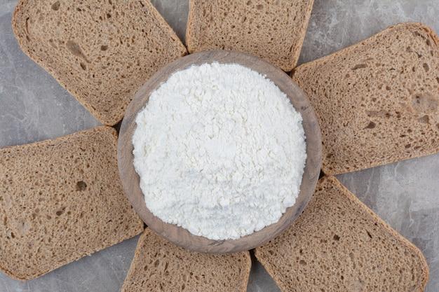 대리석 표면에 밀가루와 브라운 빵 조각