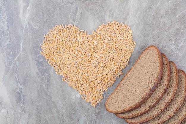 大理石の表面にオーツ麦の粒が付いた茶色のパンのスライス