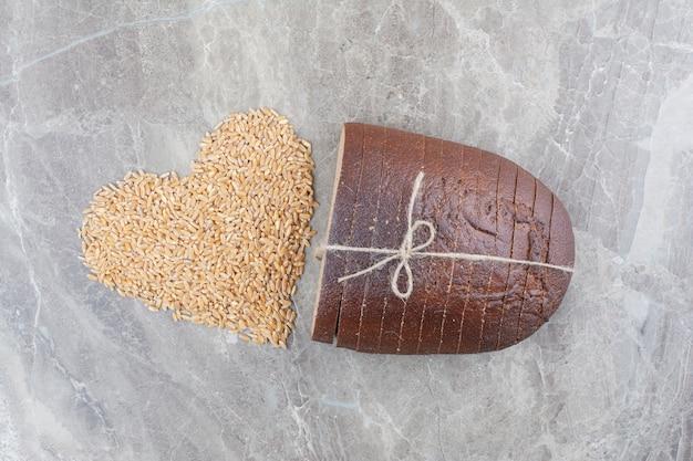 대리석 표면에 귀리 곡물과 브라운 빵 조각
