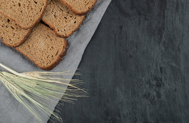 회색 배경에 밀을 넣은 갈색 빵 조각.