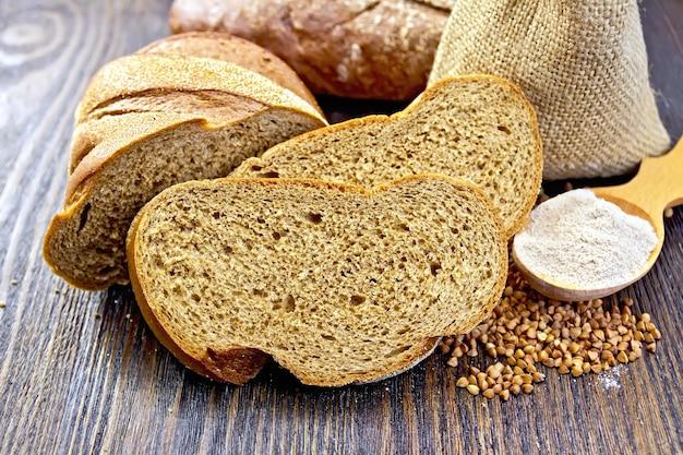 そば粉のパンのスライス、木の板の背景にスプーンで割りと小麦粉の袋