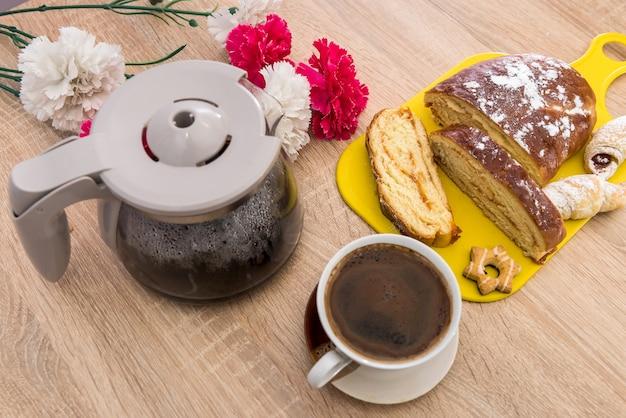 おいしい朝食のためのコーヒーのカップと粉末とパンのデザートのスライス。新鮮な甘いパイ