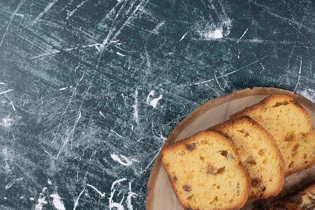 大理石の背景にレーズンとケーキのスライス。高品質の写真
