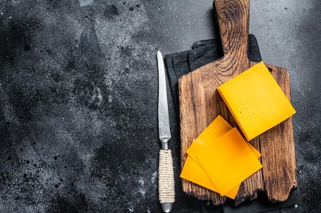 木製のまな板にチェダーチーズのスライス。黒の背景。上面図。スペースをコピーします。