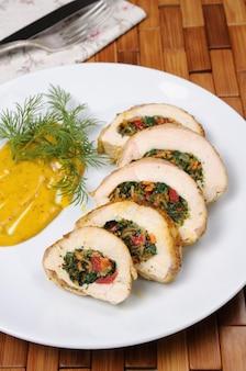 Ломтики куриной грудки, фаршированные шпинатом, морковью, перцем, помидорами на тарелке