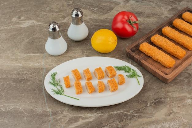 Ломтики куриных наггетсов с помидорами, лимоном, солью и перцем.