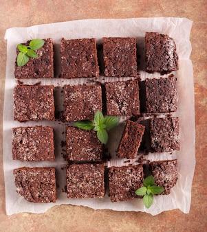 チョコレートケーキのスライス、ベーキングペーパー上のブラウニー