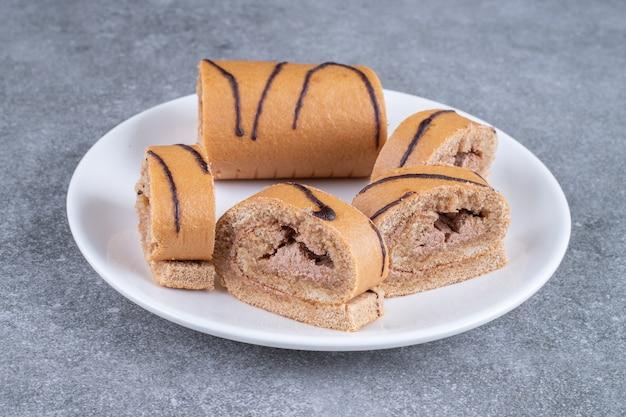 白いプレートにチョコレートロールケーキのスライス