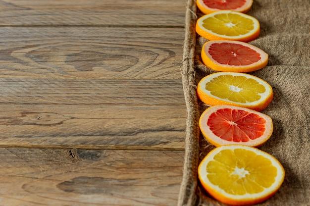 Дольки цитрусовых подряд. продовольственный фон. апельсины и грейпфруты на мешковине.