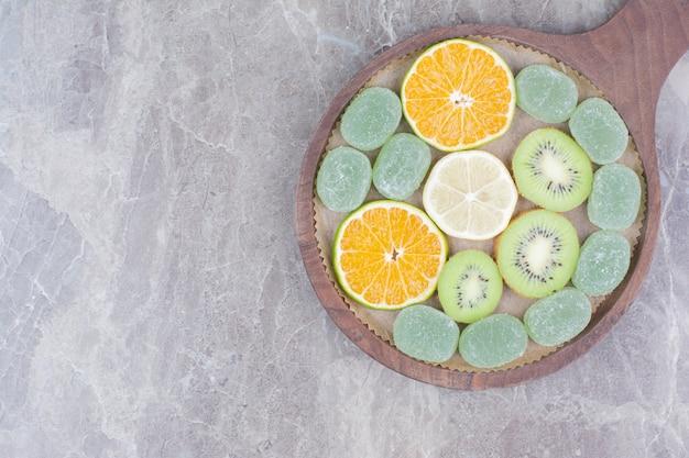 木の板に柑橘系の果物、キウイ、キャンディーのスライス。