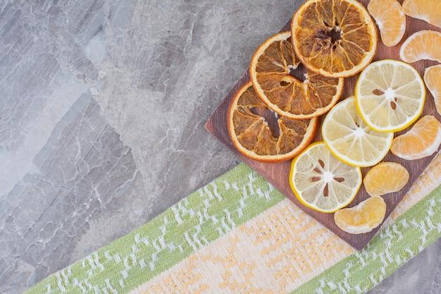 식탁보와 나무 보드에 감귤 류의 과일 조각.