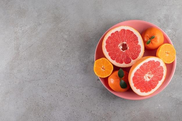 ピンクのボウルに置かれた柑橘系のオレンジとグレープフルーツの果物のスライス