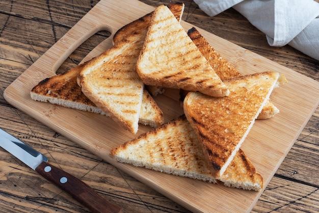 まな板、木製の素朴な背景のサンドイッチのためのサクサクのパントーストのスライス。閉じる。