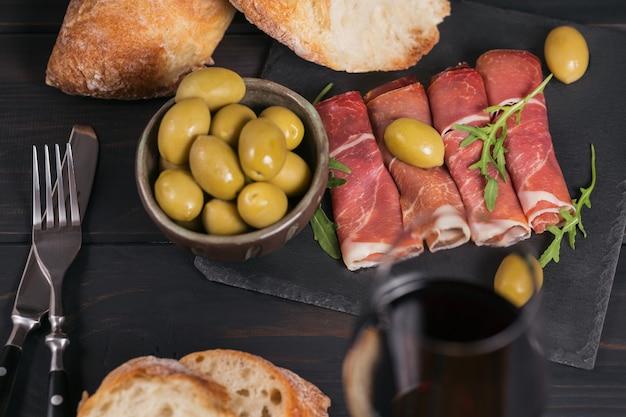 生ハムまたはスペインのハモンセラーノまたはイタリアの生ハムのスライスと赤ワインのグラス