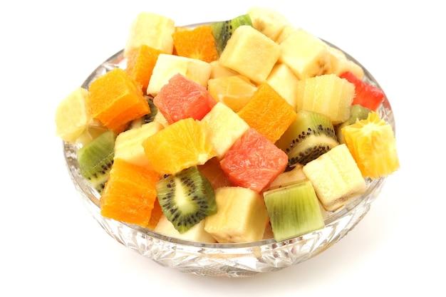 白い背景の上のプレートに立方体の形でさまざまな果物のスライス。果物の便利なビタミン食品