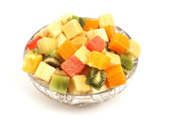 白い背景の上のプレートに立方体の形でさまざまな果物のスライス