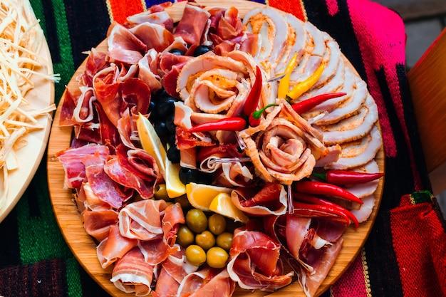 Кусочки разных видов мяса на деревянной тарелке, украшенной лимонными оливками и перцем свадебный вид сверху