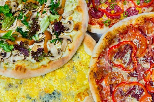 Кусочки разных видов пиццы на белом фоне