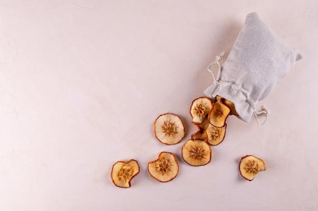 環境にやさしい袋に入ったドライフルーツのリンゴのスライスは、明るい表面にあります。