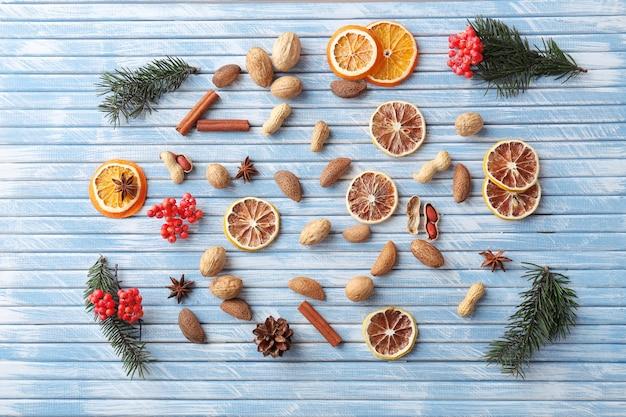 カラーの木製の背景にナッツとスパイスと乾燥オレンジとレモンのスライス