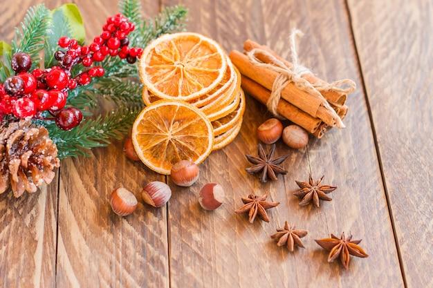 오래된 소박한 나무 배경, 건강에 좋은 음식을 요리하거나 굽기 위한 향신료와 말린 오렌지 조각.