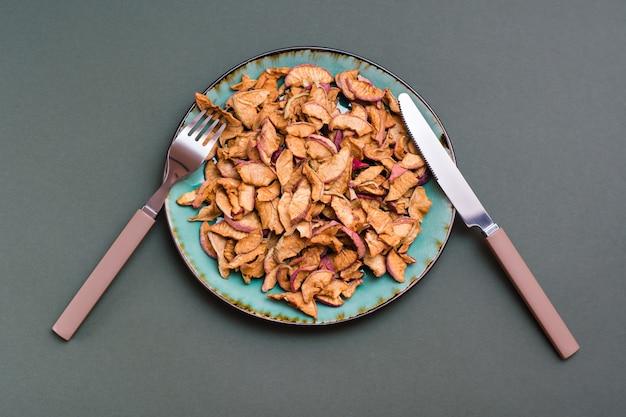 皿に乾いたリンゴのスライスと緑の背景にカトラリー。健康的な食事