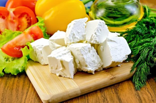 フェタチーズのスライス、トマト、黄ピーマン、レタス、油のボトル、木の板にディル
