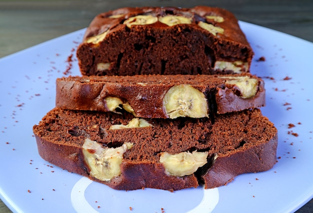 Ломтики ароматного свежеиспеченного домашнего торта с бананом из темного шоколада на тарелке