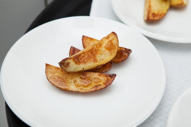 흰색 접시에 향기로운 튀긴 감자 조각