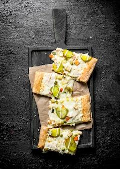 黒い素朴なテーブルの上の香りのよい野菜ピザのスライス