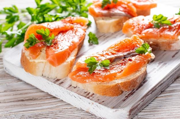 バターとサーモンと新鮮なバゲットのスライスは、木のテーブルの上の木の板で提供