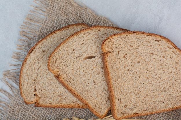 大理石の背景に焼きたての茶色のパンのスライス。
