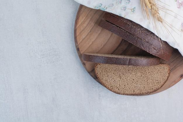 木の板に焼きたての茶色のパンのスライス。
