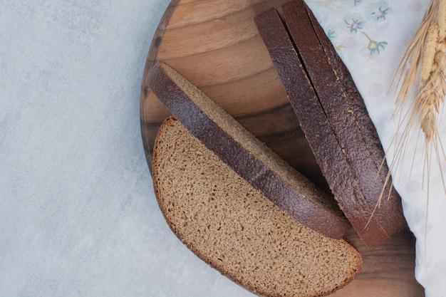 Кусочки свежего черного хлеба на деревянной доске.