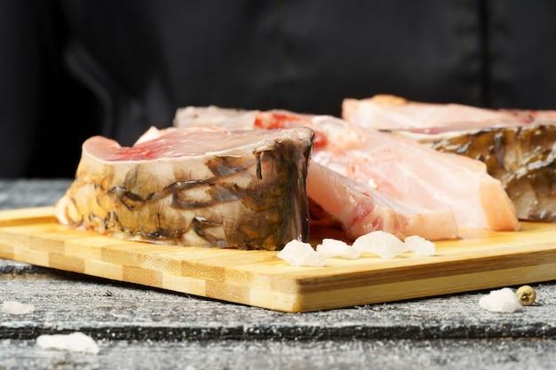 Кусочки свежего карпа, приправленные солью и перцем на разделочной доске