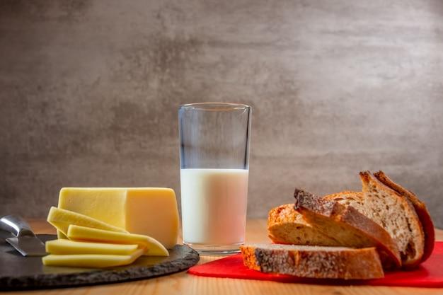 木製のテーブルにフレッシュチーズとパンのスライス。一杯の牛乳。自然食品