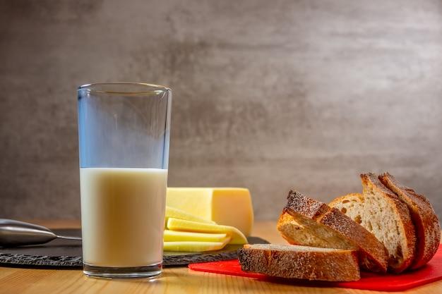 Ломтики свежего сыра, хлеба и стакан молока на деревянном столе. органическая еда