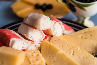 Slices of fresh cheese near tasty snacks on plate