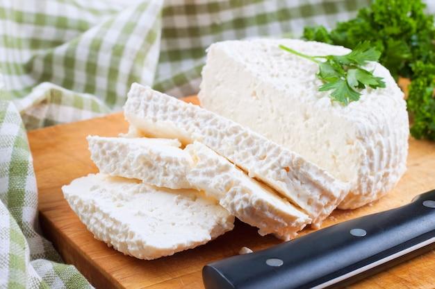 나무 절단 보드에 신선한 코티지 치즈 조각