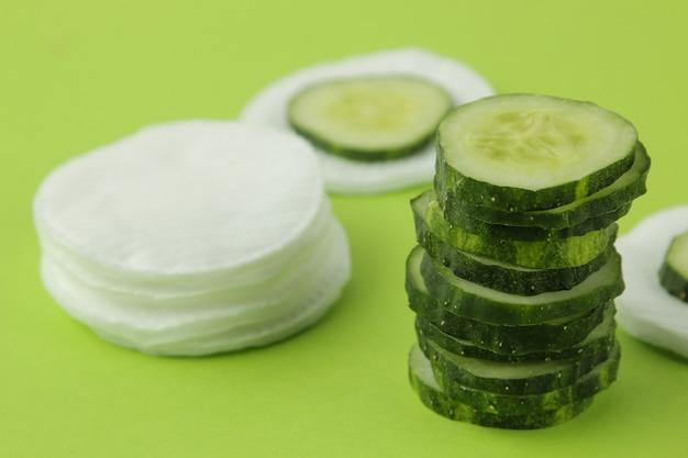 밝은 녹색 배경에 신선한 오이와 면 스폰지 조각. 오이 화장품 개념입니다. 피부 관리. 토닉 오이 추출물