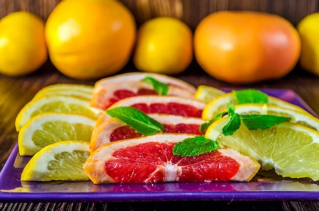 新鮮なグレープフルーツとオレンジのスライスを皿に盛り付ける