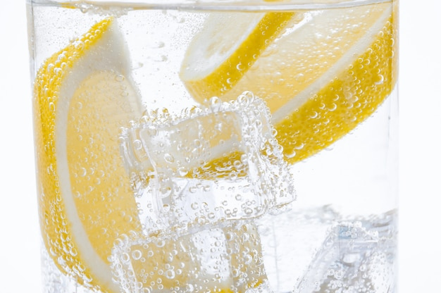 透明な水でカクテルに新鮮なジューシーレモンのスライス。