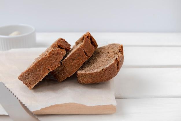 텍스트를 위한 공간이 있는 흰색 테이블에 있는 나무 판자에 신선한 호밀 빵 조각